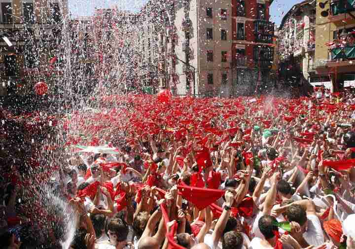 Revellers hold up traditional red scarves at the start of the San Fermin festival in Pamplona July 6, 2007.   REUTERS/Felix Ordonez Ausin  (SPAIN)